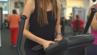 slim unrecognizable woman walks elliptical trainer isolated