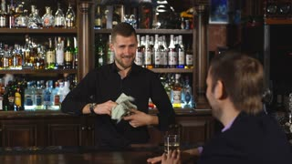 Smiling attractive young barman wiping glasses and talking to young man in bar
