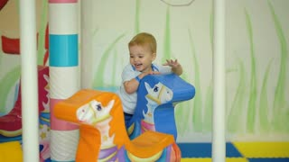 Smiling child riding a toy horse carousel