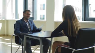 smiling the employer asks questions to the woman in the interview