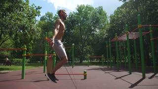 sportman man jumping rope on green lawn park