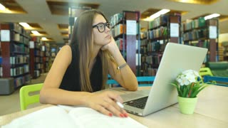 student bored in the library, working on the computer in the library, brunette with glasses