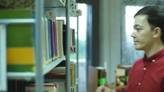 student boy chooses of a book in the library