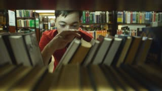 student chooses a book in the library