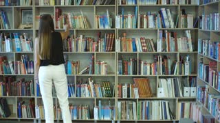 student girl chooses among the shelves of a book in the library
