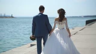 the bride and groom walk along the promenade