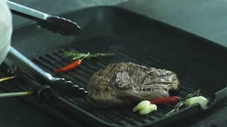 the chef flips the steak with tongs