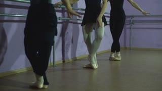 The close-up feet of a three young ballerinas in pointe shoes