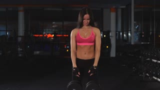 the girl does exercises on a biceps with dumbbells
