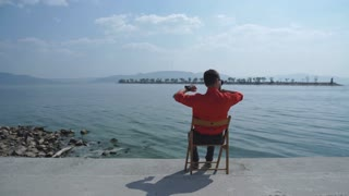the man in the red shirt sitting on the chair and enjoys stunning views of the river