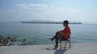 the man in the red shirt sitting on the chair and enjoys views of the river