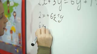 the schoolboy writes an example on the Board