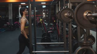 the woman squats with a barbell