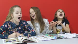 three Schoolgirls laughing at the lesson