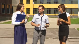three students are walking through campus and communicate