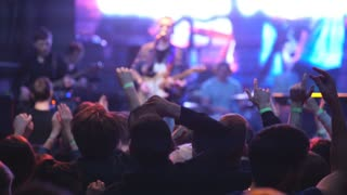 Togliatti,Russia,April 23,2016:Audience with hands raised at a music festival and lights streaming down from above the stage. Soft focus, high ISO