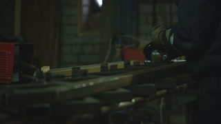 Tradesman uses an electric grinder to cut a pipe in two