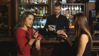 Two attractive young women meeting up in a pub for a glass of red wine sitting at a counter smiling at each other
