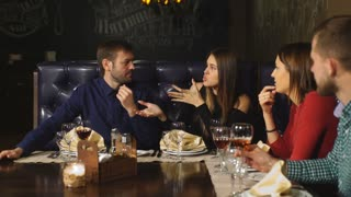 two beautiful couples actively communicate in the restaurant and waiting for your order