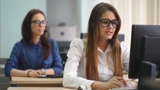 Two beautiful girls communicate with customers in a call center