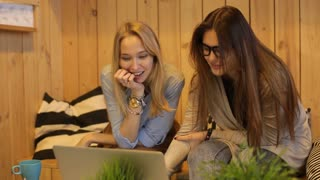 Two beautiful girls smilling and use laptop