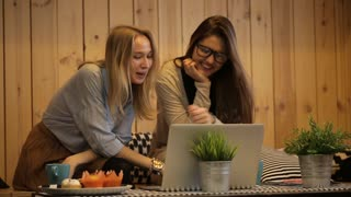 Two beautiful girls talking and use laptop
