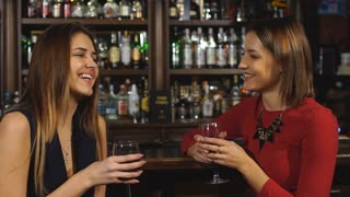 two beautiful women met at the bar and laugh in slow motion