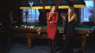 two beautiful women standing near a pool table talking to two men in the background playing pool