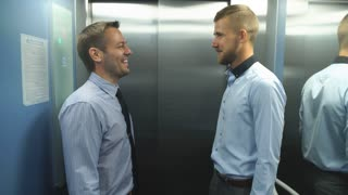 two businessmen riding the Elevator and talking to