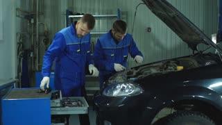 two car mechanic in uniform repairing car
