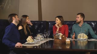 Two Couples Enjoying Meal In Restaurant Together