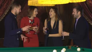 two couples talking near the pool table and drink