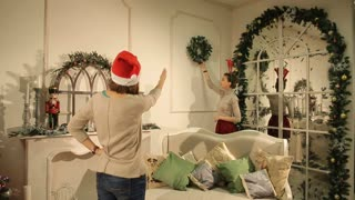 two girls decorate a room for Christmas