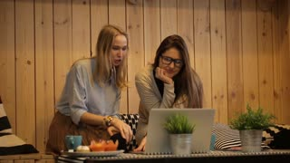 Two girls sit in cafe and looking at a laptop