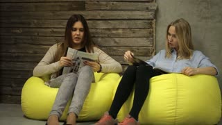 two girls talking and reading a magazine