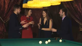 two pairs next to the pool table raise their glasses and drink,party