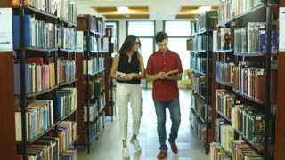 two students walk through the library in search of books