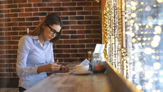 a beautiful young businesswoman works in a cafe and signs contracts