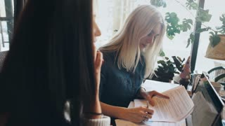 a company businesswomen actively discusses a business project in a cafe and signs a contract
