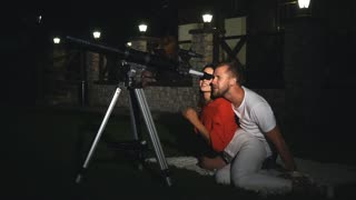 a couple looks through a telescope