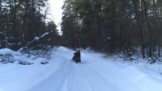 A couple on a snowmobile in the woods. Winter sports and entertainment.