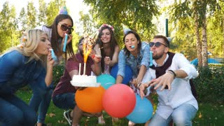 a group of friends in party hat and party horn having fun and celebrating the birthday