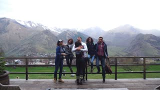a group of friends on the lookout hug mountains in the background