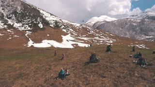 a group of tourists sits on a mountain and looking at the glacier