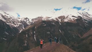 a group of travelers on the edge of a mountain