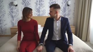 a happy young couple falls on the bed