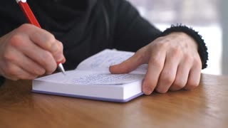 a male freelancer writes a note in a notebook on a wooden table