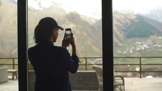 a woman tourist takes a picture of the mountains on the telephone