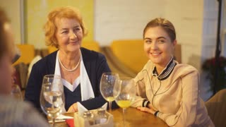 adult granddaughter and grandmother talking at a family dinner