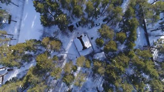 An aerial view of a house covered in snow in the woods